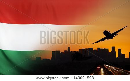 Travel and transport concept with skyline silhouette highway traffic and airplane at sunset merged with real fabric flag of Hungary