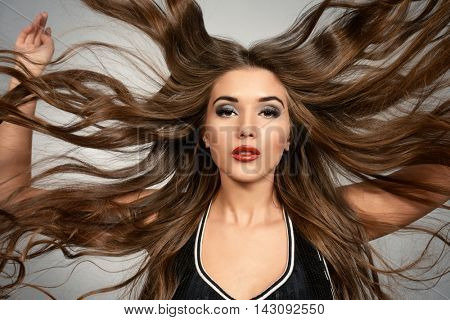 Portrait of a beautiful young woman with long fluttering hair. Hairdressing, hairstyle. Healthy long wavy hair. Sexy model with black smoky eyes.