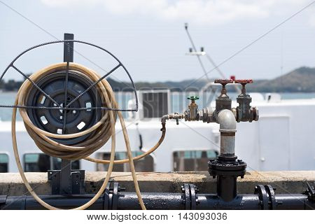 Water hose by dock pier and water valve