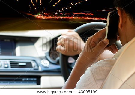 Concept dangerous Man Driving and using cell phone at night