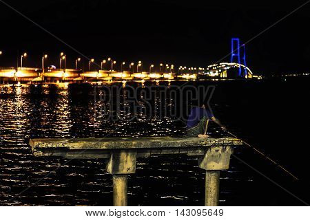 Fisherman on a concrete pylon catch fish at night. In backround Suramadu Bridge at Twilight time Surabaya Indonesia. Is the longest Bridge in Indonesia.