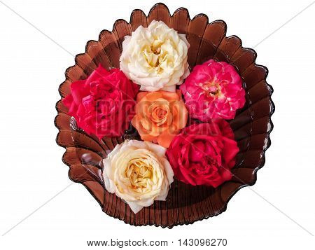 White tea, orange and red roses floating in a glass vase with water, top view. Isolated on white background