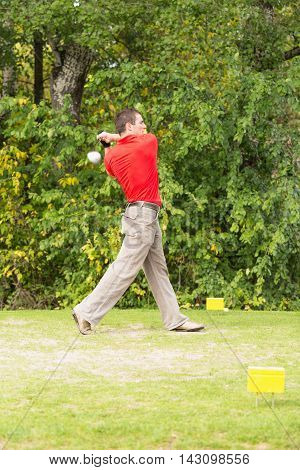 Golfer teeing off, vertical image, toned image
