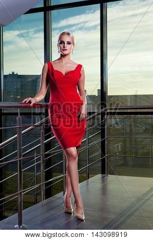 Young beautiful glamorous blonde girl posing on the background of a glass showcase.