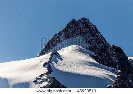 Snowy mountain peak. Mountaineering rock climbing. Group of mountaineers climbing mountain ridge to top