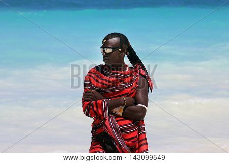 Zanzibar Tanzania - January 5 2016: Young massai man with colorful traditional clothes headdress and self made shoes walking through the water on the Nungwi beach.