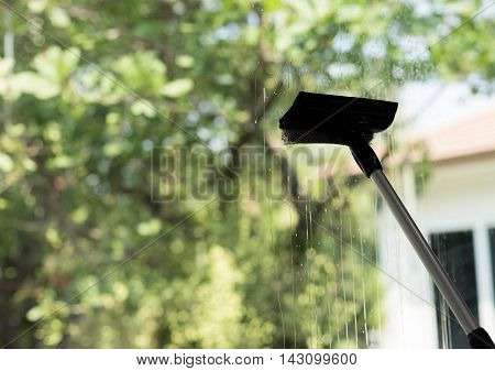 Silhouette of Window cleaner using a squeegee to wash a window