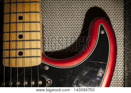 Black and red electric guitar over amplifier device. Closeup