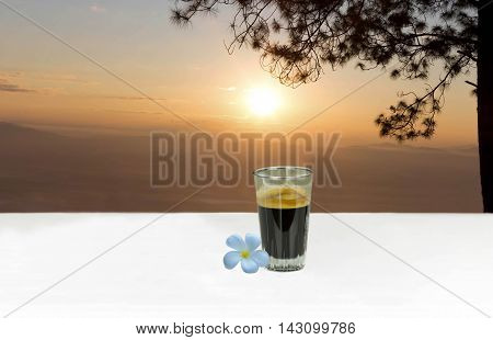 Espresso coffee shot on table with plumeria flower on sunset or sunrise background