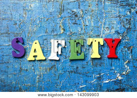 safety word written on wood abc letter at blue abstract background.
