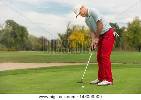Golfer putting the ball in hole, toned image,