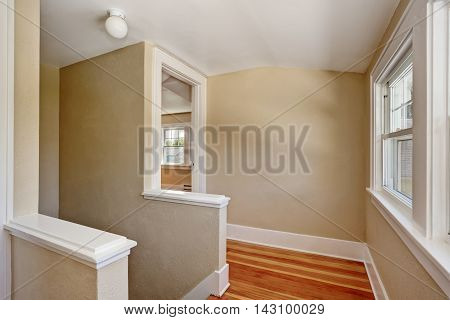 Hallway Interior With Beige Walls And Hardwood Floor.