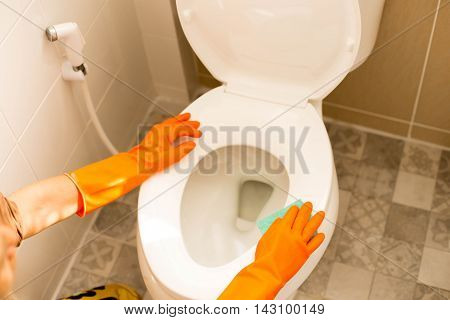 Hands on orange gloves cleaning a lavatory in the wash room