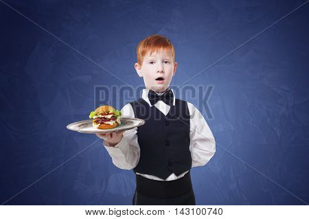 Little surprised waiter stands with tray serving hamburger. Redhead child boy in suit plays restaurant servant, gives burger at blue background