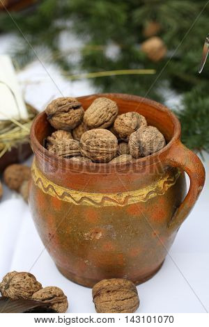 Walnuts in a ceramic pot on the table