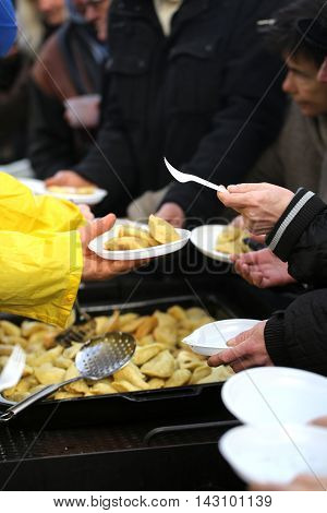 CRACOW POLAND - DECEMBER 20 2015: Christmas Eve for poor and homeless on the Central Market in Cracow. Every year the group Kosciuszko prepares the greatest eve in the open air in Poland