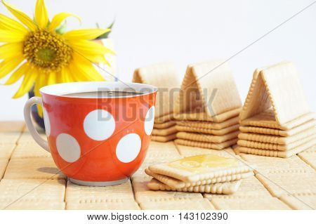 Biscuit with honey. House of crackers. Still life of crackers and a cup of black coffee. Red cup with white polka dots.