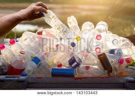 Hand holding recyclable plastic bottle in garbage bin with sunset light