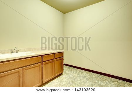 Empty Bathroom Interior With Vanity Cabinet And Tile Floor.