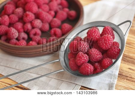 Fresh raspberry in sieve and plate, closeup