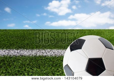 sport, football and sports equipment concept - close up of soccer ball over playing field and blue sky background