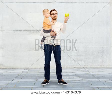 family, childhood, fatherhood, healthy eating and people concept - happy father and and little son with green apple over urban street background