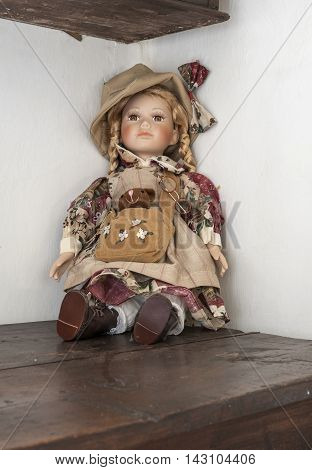 antique doll above a wooden table with white background wall