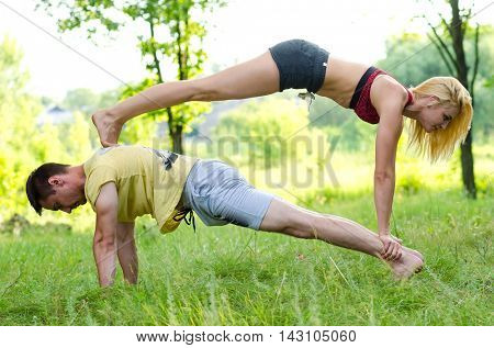 Young couple doing yoga at the park. Acroyoga.