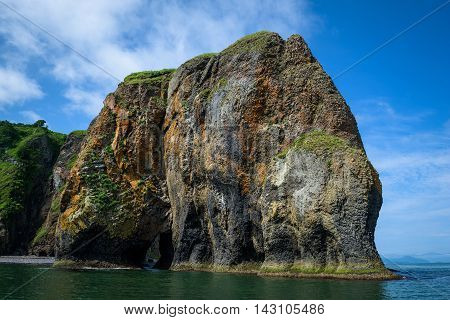 Green rocky cliffs form the coastline of the Avacha Bay, Kamchatka, Russia