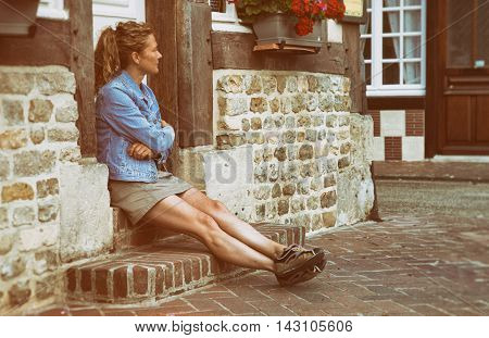 Woman sitting watching a house in Norman