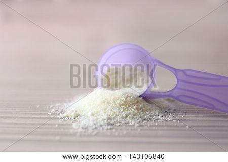 Baby milk formula on in purple spoon wooden background