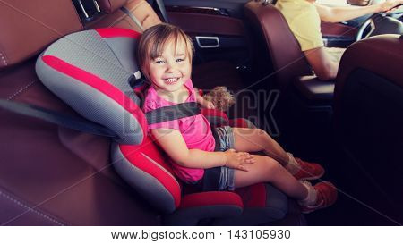 family, transport, safety, road trip and people concept - happy little girl sitting in baby car seat and father driving