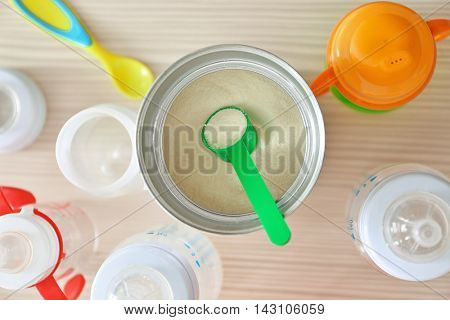 Feeding bottles and baby milk formula on wooden background