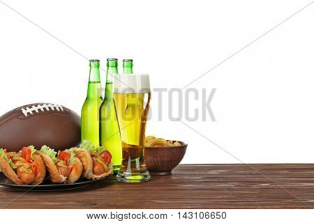 Glass of beer, bottles, ball and snack on wooden table with white background