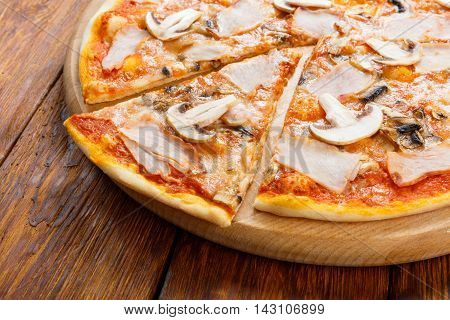 Delicious italian pizza with mushrooms and smoked chicken meat - thin pastry crust at wooden background, one piece cut