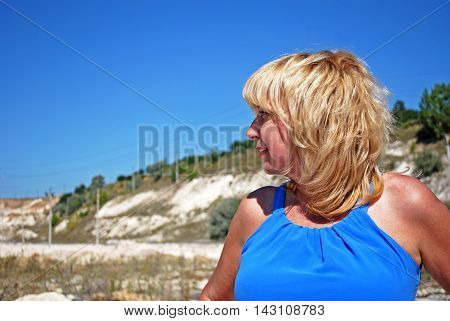 Blonde woman in blue dress on the background of the surrounding area of the chalk quarry.