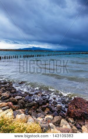 Piles of ruined pier protruding from the water. Strait of Magellan summer day. Waterfront, Punta Arenas