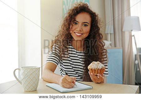 Beautiful African girl counting calories