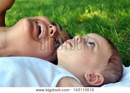 Mother and baby sharing dying down on the grass looking the sky and trees.