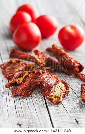 Fresh and dried tomatoes on old table.
