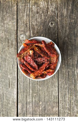 Healthy dried red tomatoes in bowl. Top view.