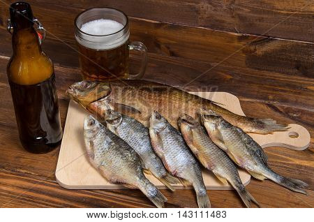 Dry fish on a wooden background with beer