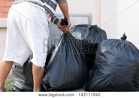 Woman Taking Out Garbage In black bags