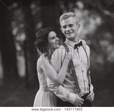 groom gently embraces her groom in the forest