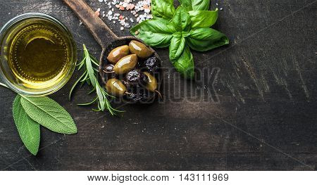 Green and black Mediterranean olives in old cooking spoon with olive oil and herbs over dark rustic wooden background, top view, copy space, horizontal composition
