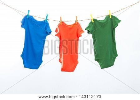 Colorful clothes hanging on the rack isolated on white background.