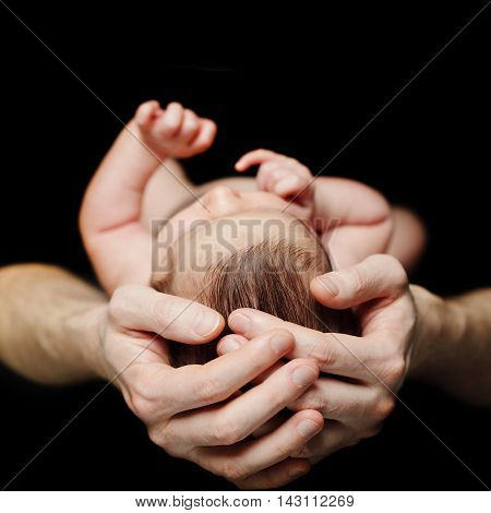 Father holding his newborn baby. Birth concept