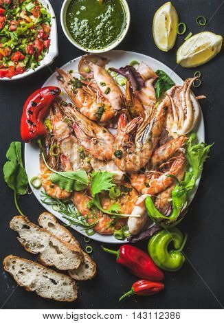 Plate of roasted tiger prawns and pieces of octopus with fresh leek, vegetable salad, peppers, lemon, bread and pesto sauce over black background, top view, vertical composition