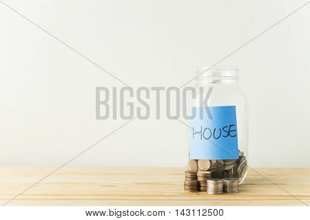 Money jar with coins on wood table Saving for House Concept
