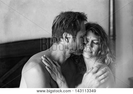 Black and white shot of a cute couple in love. Man tenderly kissing a woman on the bed.